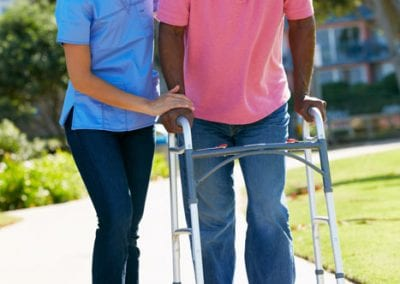 CarerHelpingSeniorManWithWalkingFrame