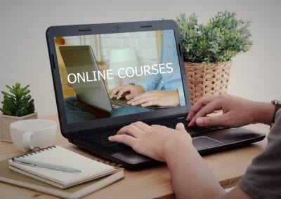 Man-hand-typing-laptop-with-online-courses-on-screen