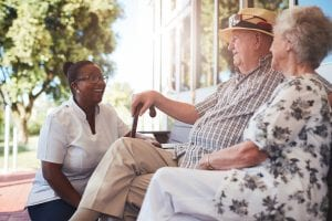 caregiver talking to a senior couple